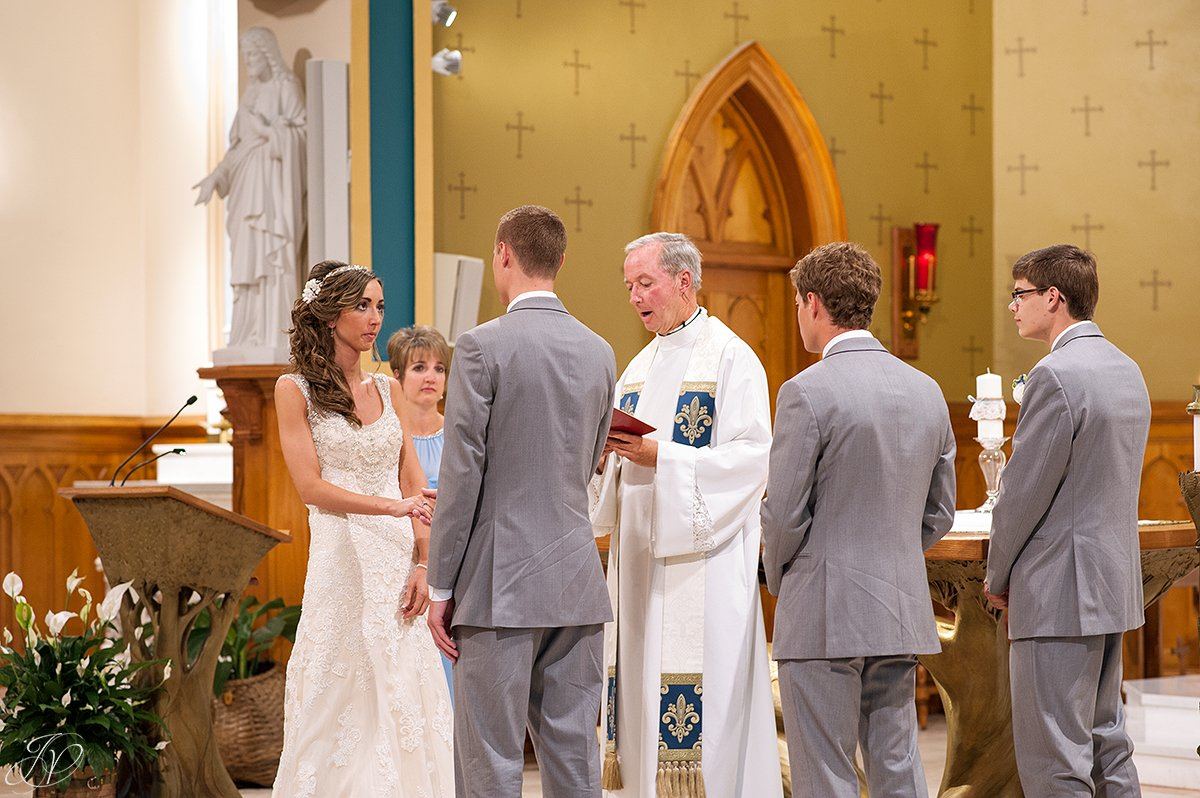 bride and groom exchanging vows during church ceremony