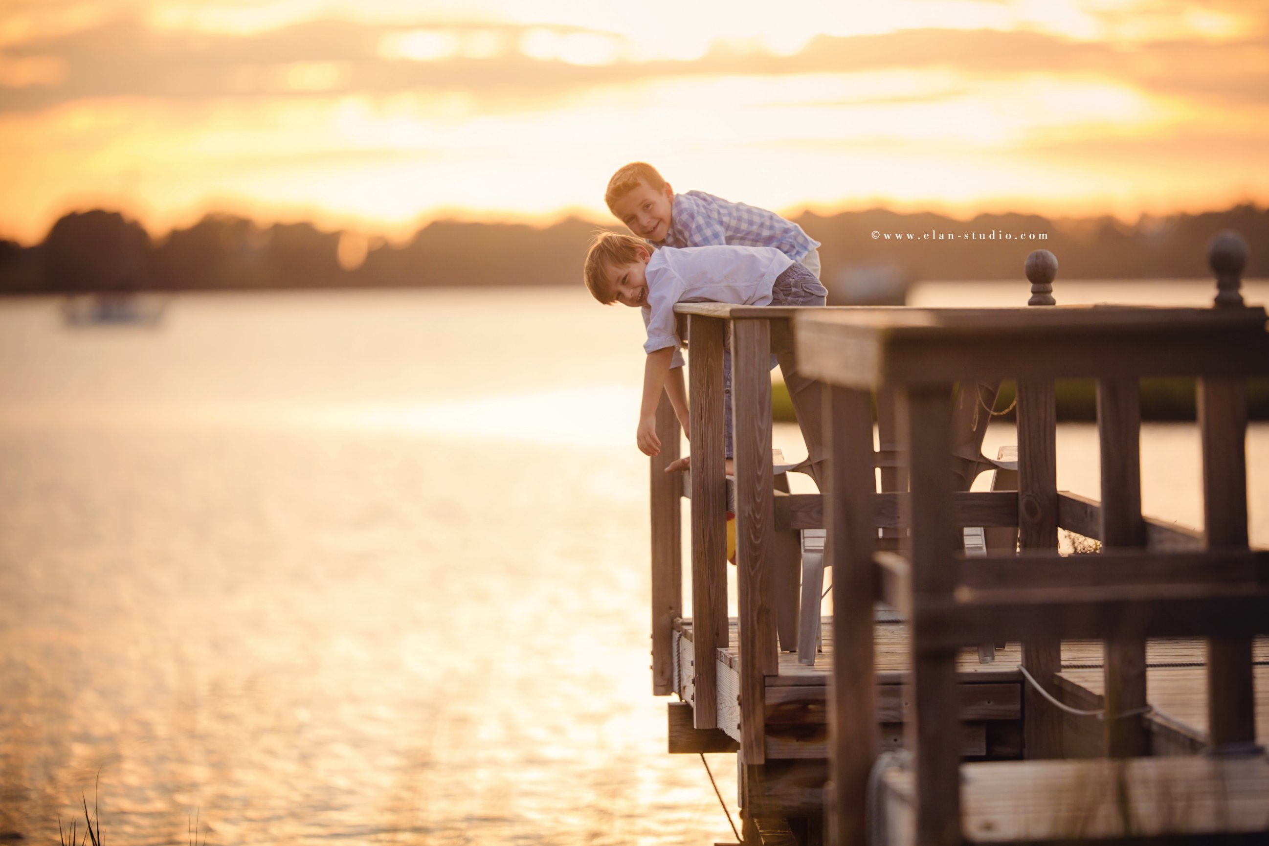two boys playing on a dock