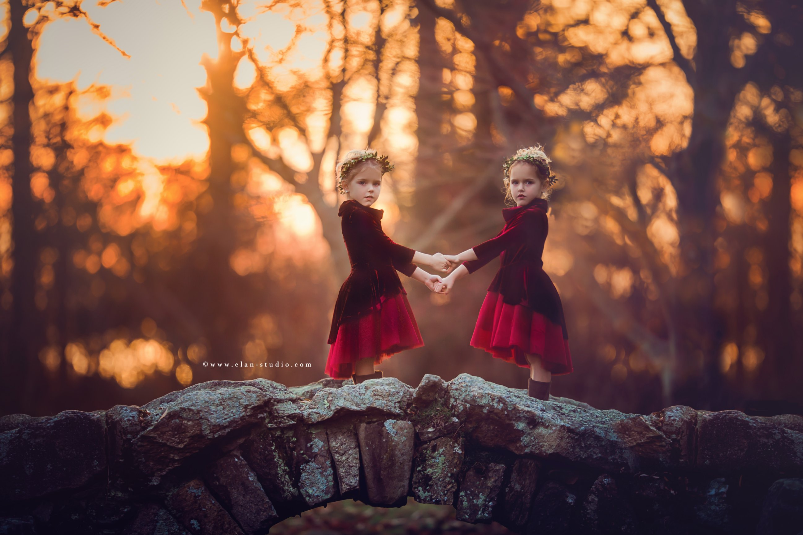 twin girls wearing matching cranberry colored dresses against natural autumn background