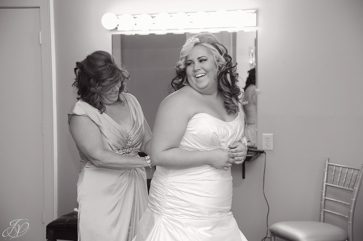 fun shot of bride's mom helping bride get dressed