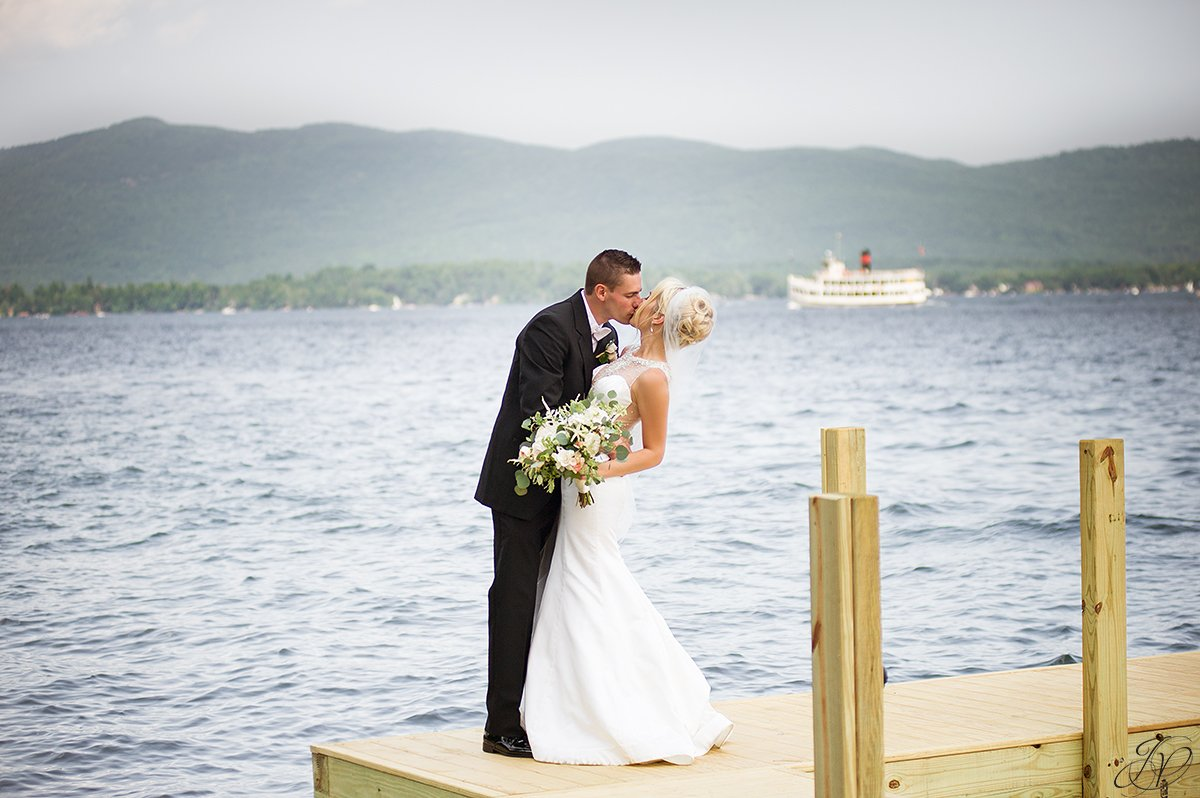 groom dipping bride lakefront lake george lake george