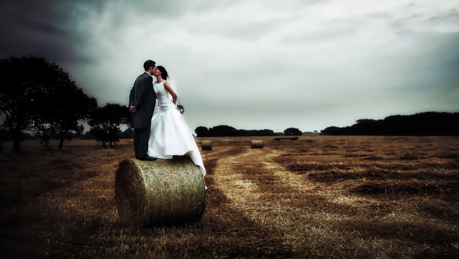 Bride and Groom on haystack, unusual wedding photography