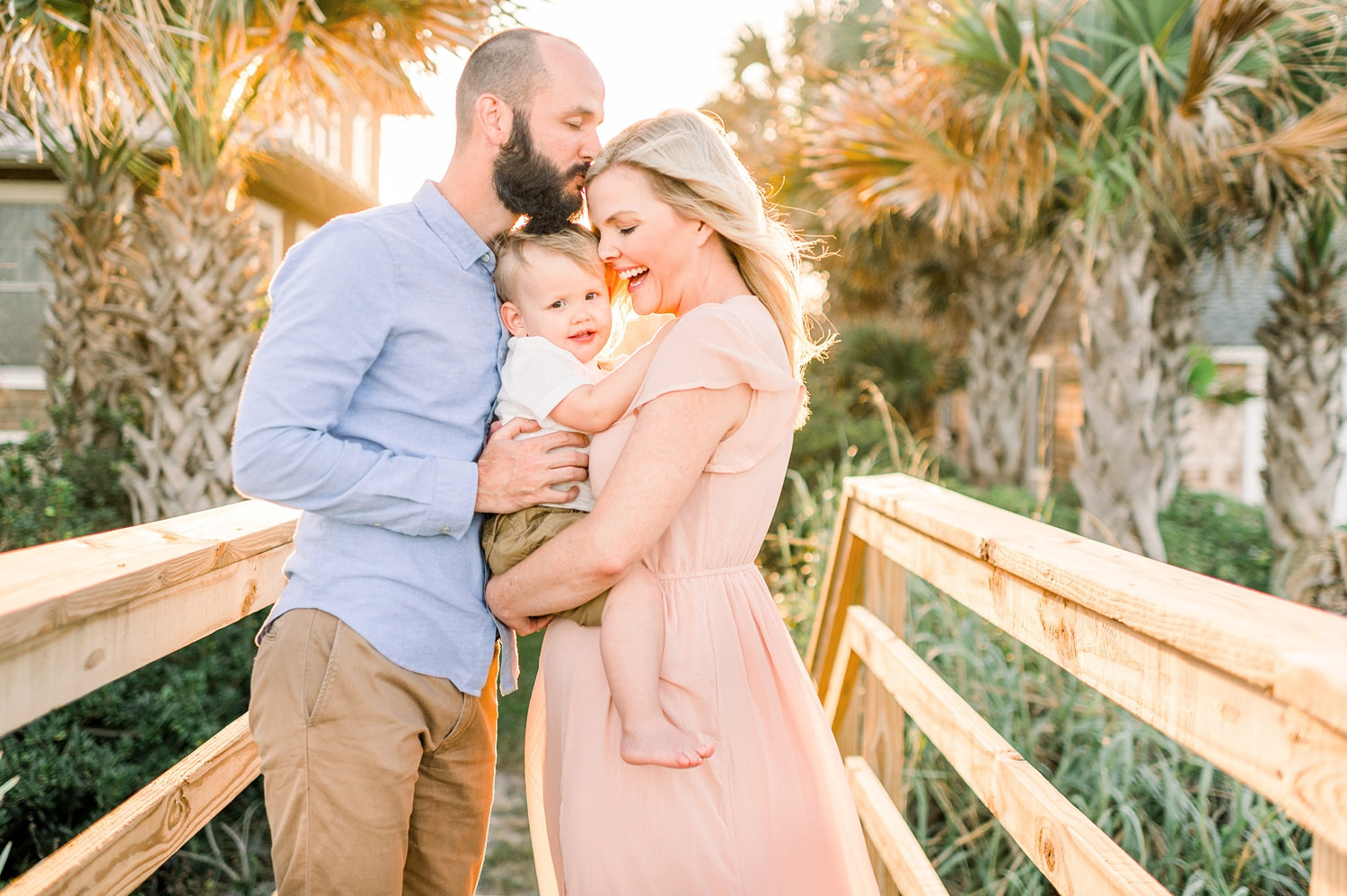 father kissing mother's forehead, man with a beard, little boy, blonde woman, Florida beach, Rya Duncklee