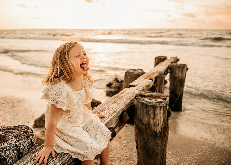silly little girl sitting on beach pilings, Naples Beach, Florida, Ryaphotos