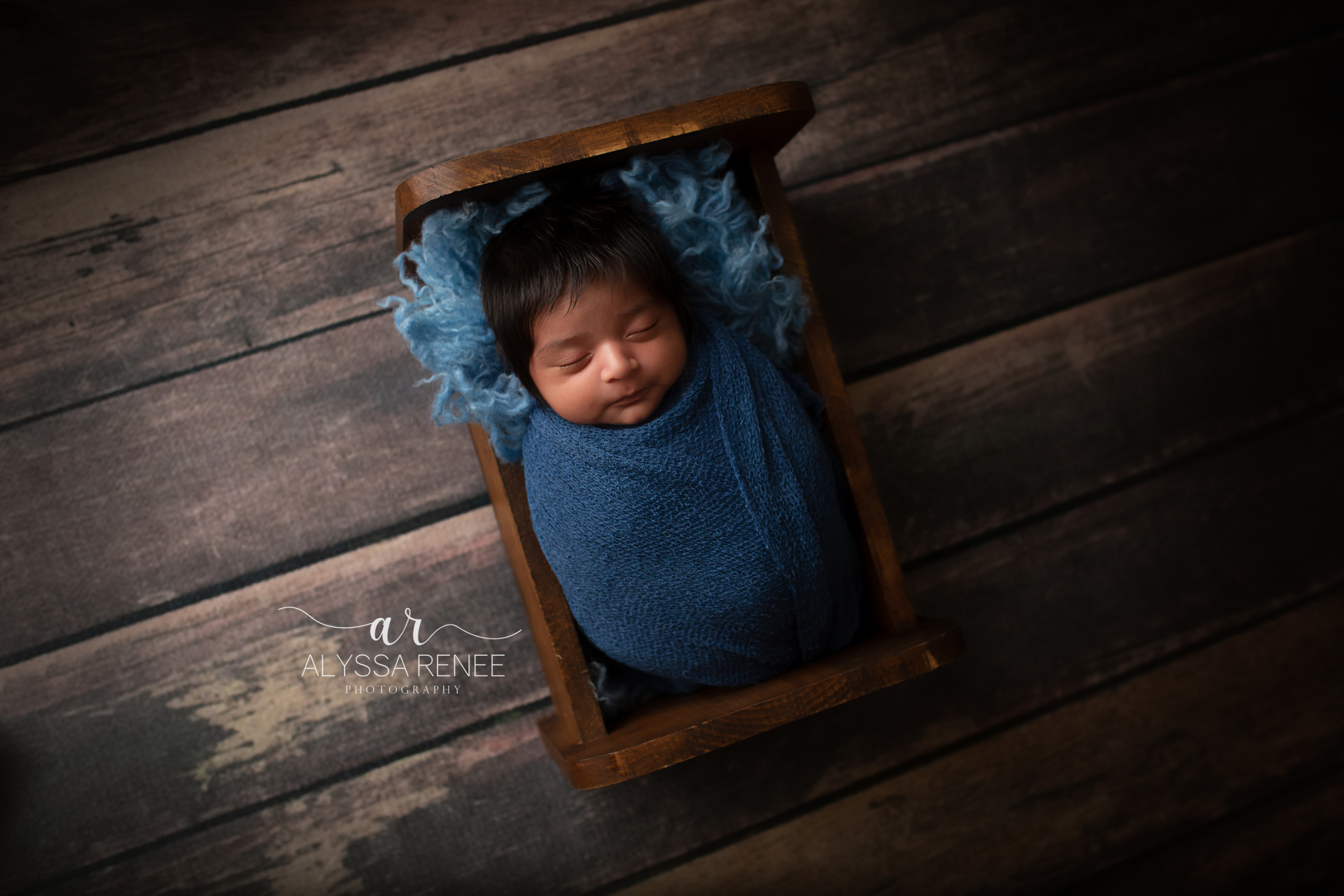 Newborn photo with baby swaddled in blue blanket from our collection in a crib with blue faux fur lining