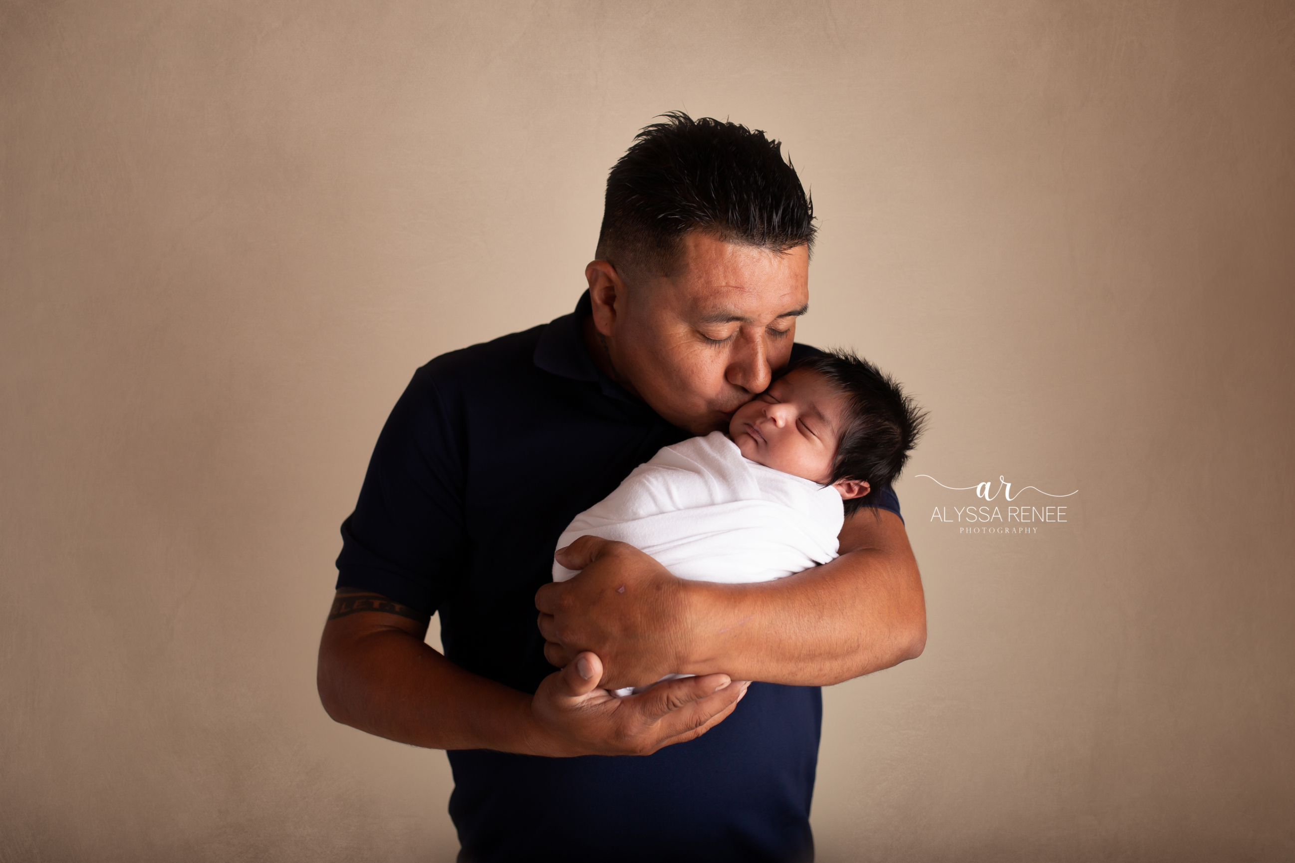 Portrait of dad kissing swaddled newborn