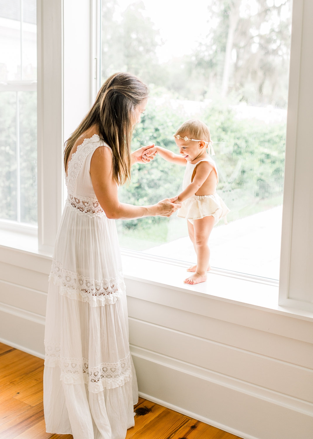 mom and toddler daughter standing together, holding hands, window portraiture, Rya Duncklee Photos