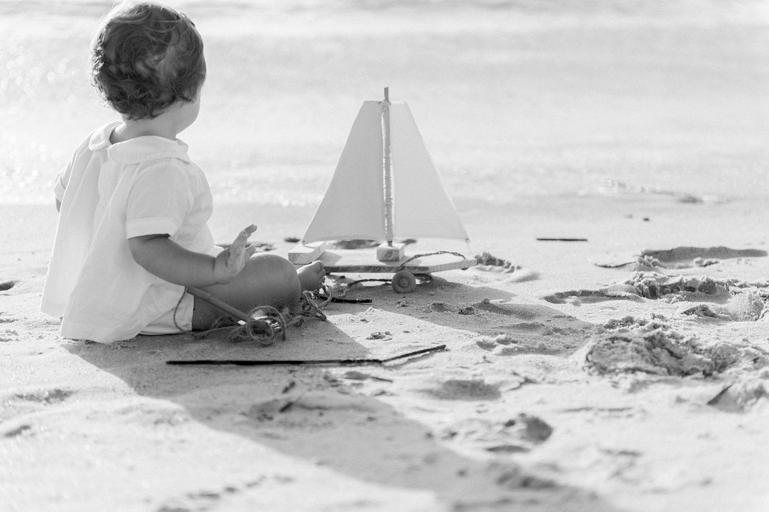 black and white portrait of a one year old little boy with a boat pull toy on the beach