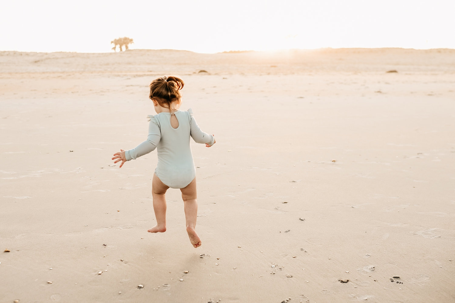 toddler girl jumping in the sand on the beach, Florida, Ryaphotos