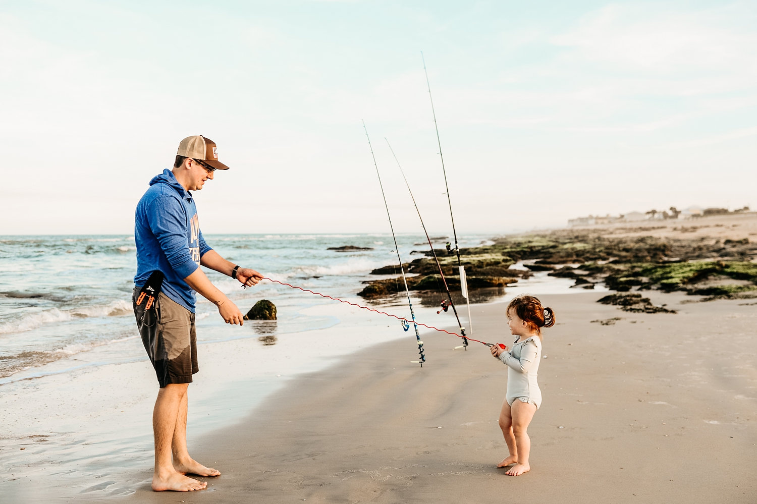 father and little girl having fun fishing on a Florida beach, Ryaphotos