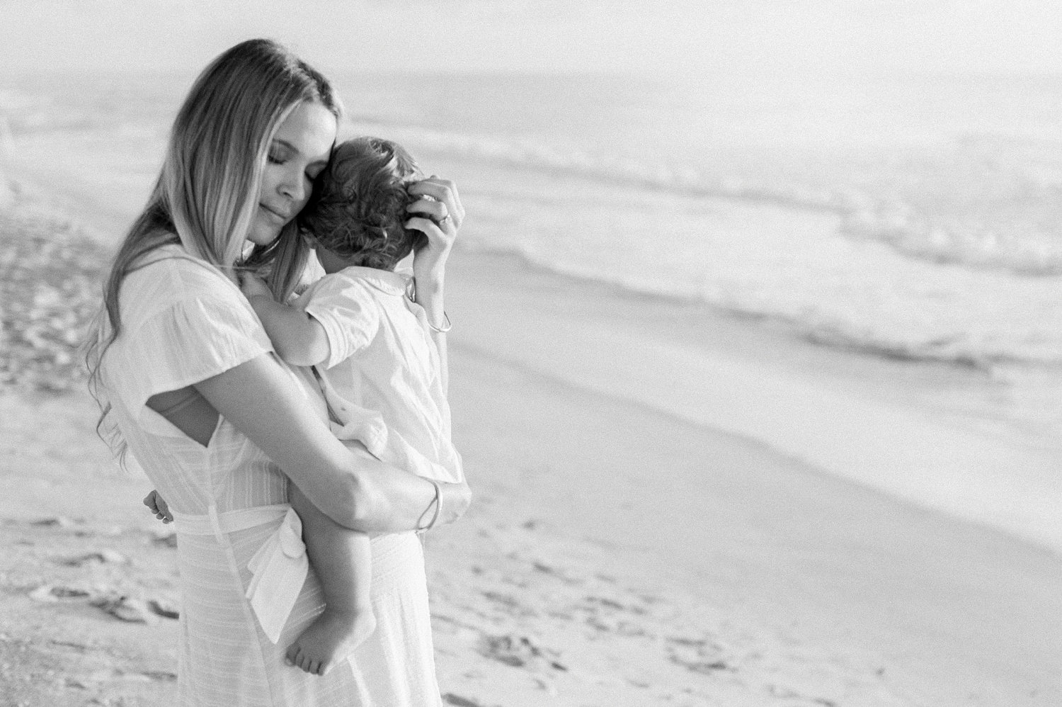 black and white image of mother embracing her little boy along the coast